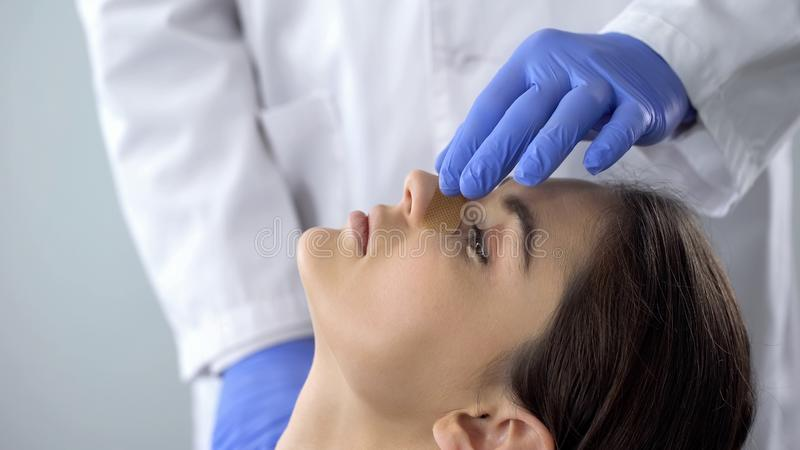 Doctor examining patient nose after rhinoplasty surgery, medical aid, healthcare royalty free stock photo