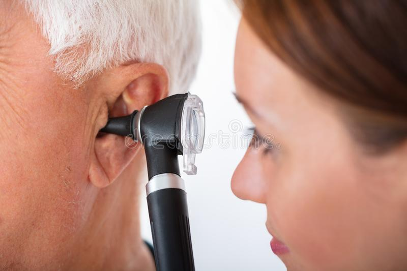 Doctor Examining Patient`s Ear With Otoscope stock image