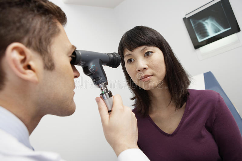 Doctor Examining Patient's Eye. Male doctor examining female patient's eye in the clinic royalty free stock photography