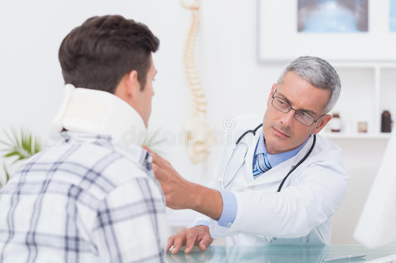Doctor examining patient wearing neck brace. In medical office royalty free stock photography