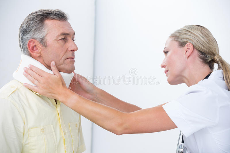 Doctor examining patient wearing neck brace. In medical office royalty free stock image
