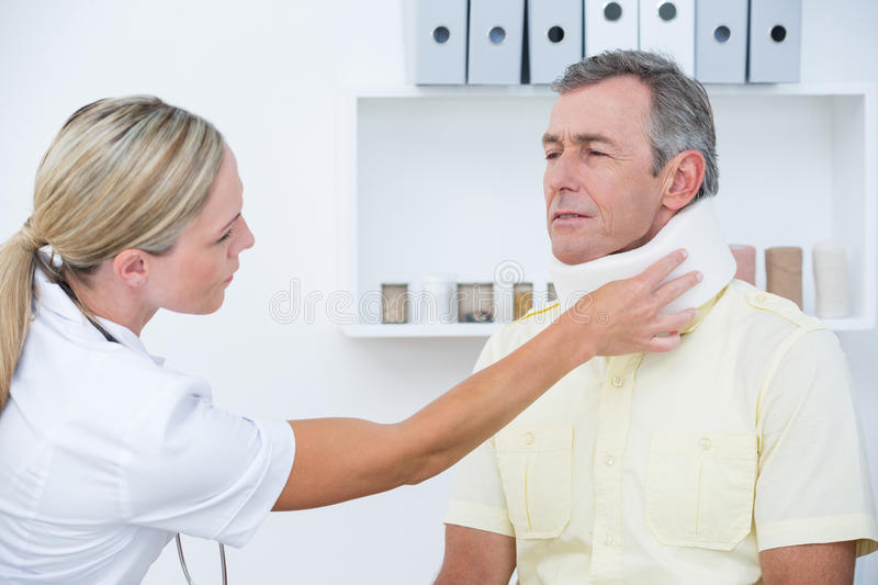 Doctor examining patient wearing neck brace. In medical office royalty free stock photos