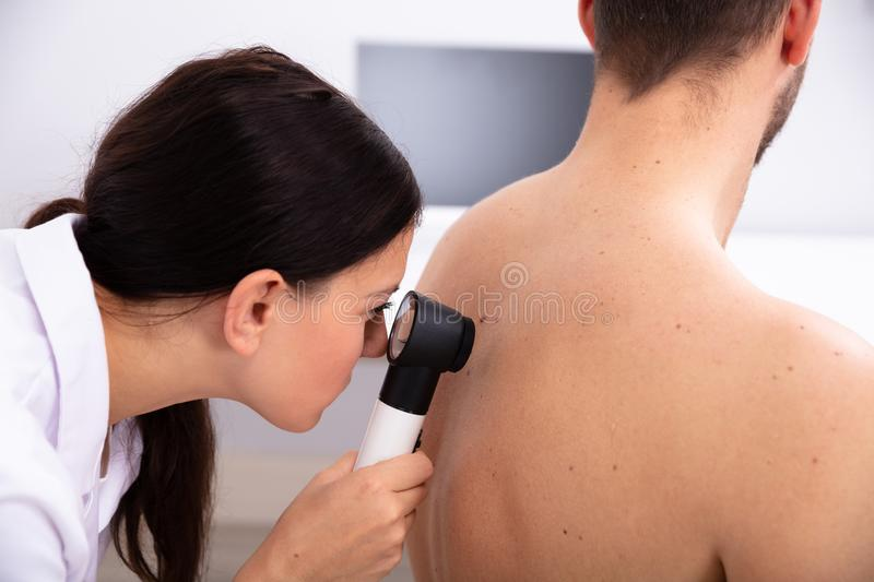 Doctor Examining Pigmented Skin On Man`s Back royalty free stock photography