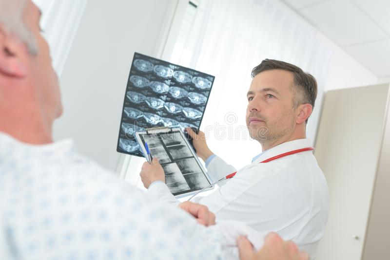 Doctor examining x-ray image in hospital room. Doctor royalty free stock images