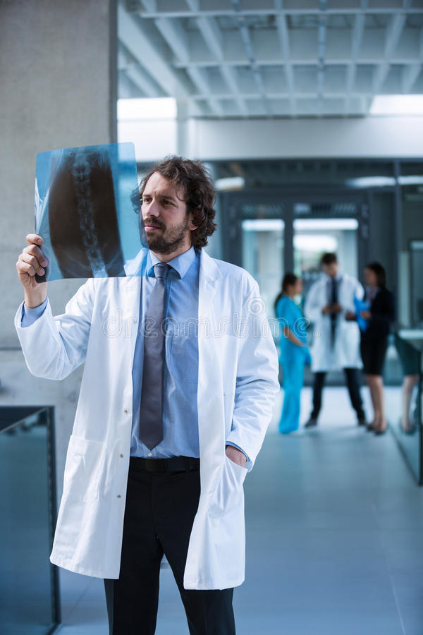 Doctor examining X-ray report. At the hospital premises stock photos