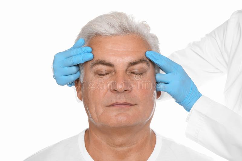 Doctor examining senior man face before cosmetic surgery stock photography