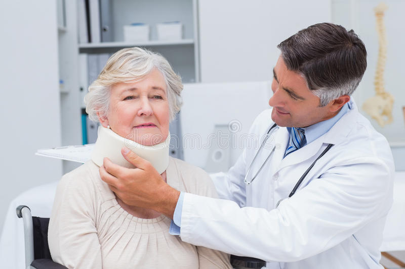 Doctor examining senior patient wearing neck brace. Male doctor examining senior patient wearing neck brace in clinic stock image