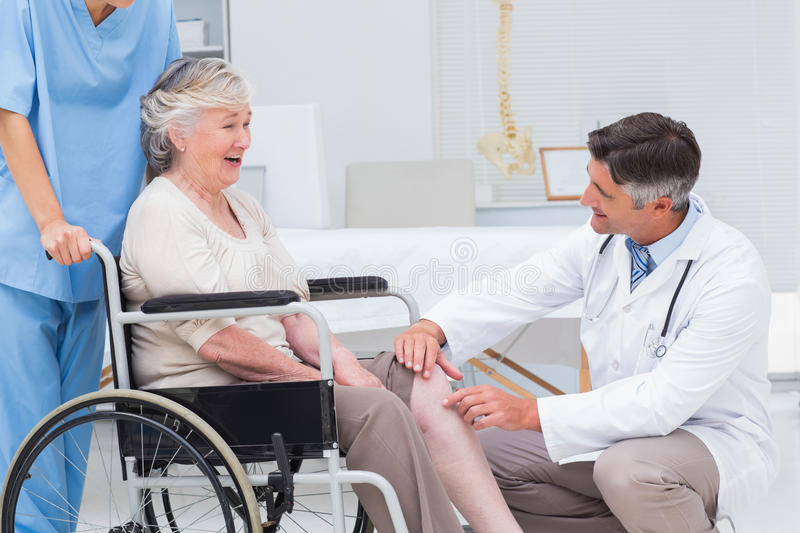 Doctor examining senior womans knee royalty free stock images