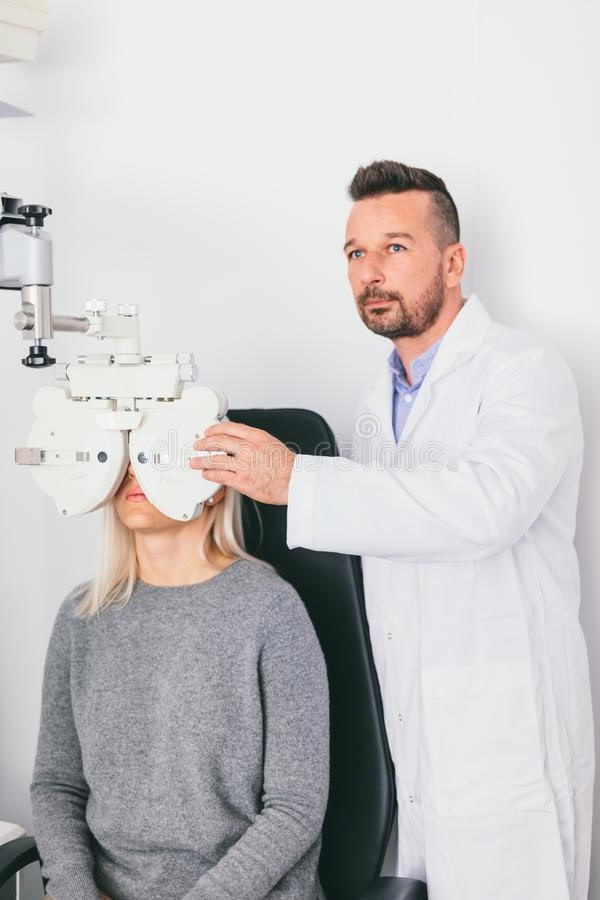 Doctor examining woman`s eyesight. With special equipment. Medical test, ophthalmology stock photo