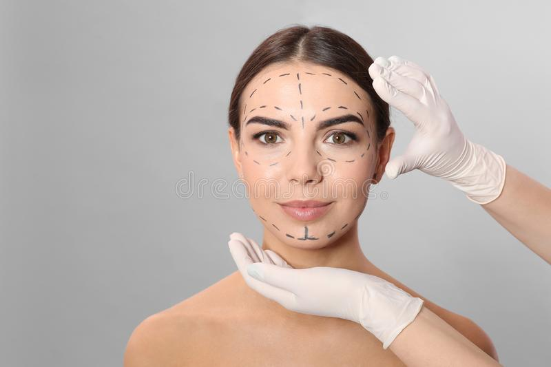 Doctor examining woman`s face with marker lines for plastic surgery operation royalty free stock photos