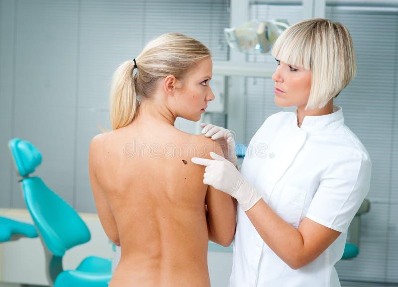 Doctor examining woman skin royalty free stock photo