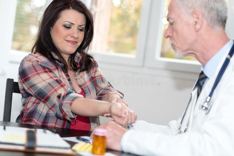 Doctor examining wrist of a female patient stock image