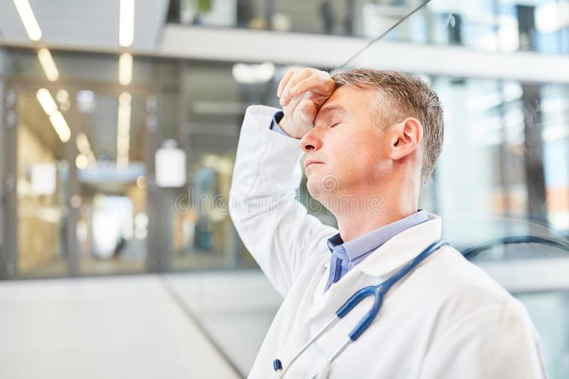 Doctor is exhausted in the emergency room. Doctor stands exhausted with his hand on his forehead in the emergency department in the hospital royalty free stock photography