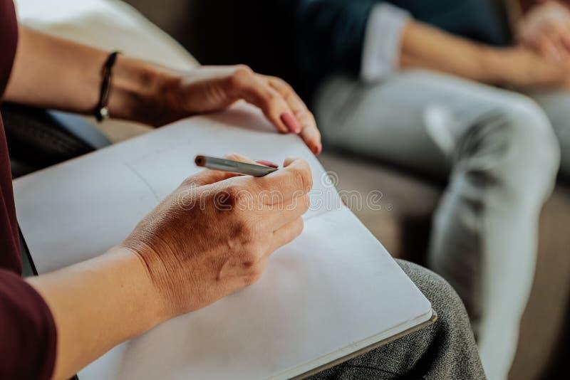 Doctor experimentado enfocado de la psicología que anota notas sobre problemas imágenes de archivo libres de regalías