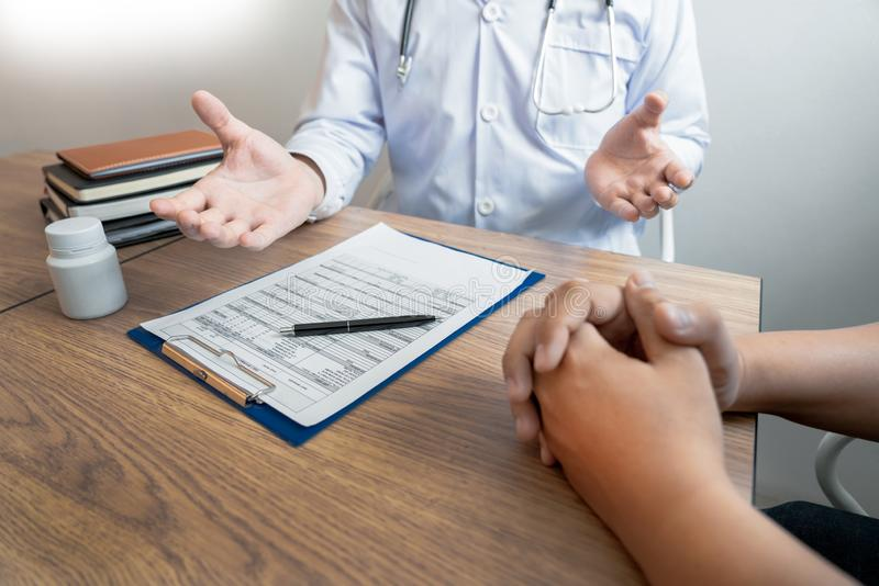 Doctor explaining and giving a consultation to a patient medical informations and diagnosis about the treatment for condition in. Hospital, medical ethics royalty free stock image
