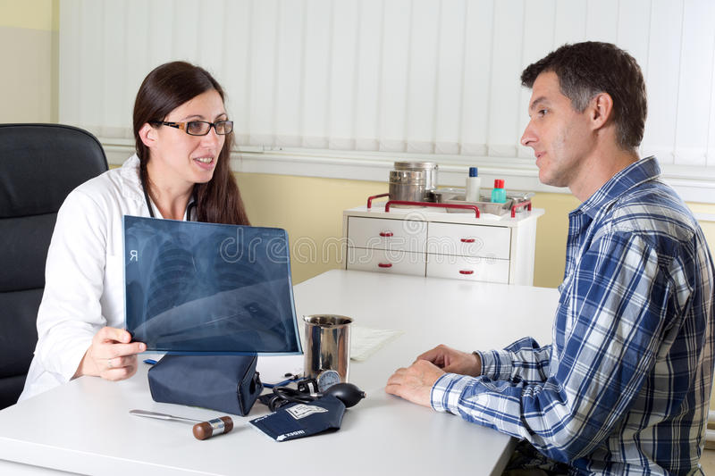 Doctor Explaining Lung X-ray Results to Middle Aged Patient in Consulting Room stock image