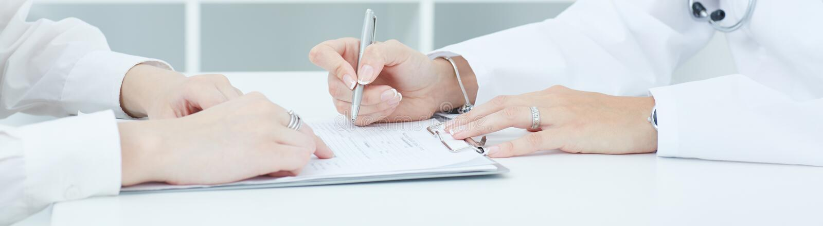 Doctor explaining to her female patient how to fill the medical form at office. Just hands over the table. stock photo