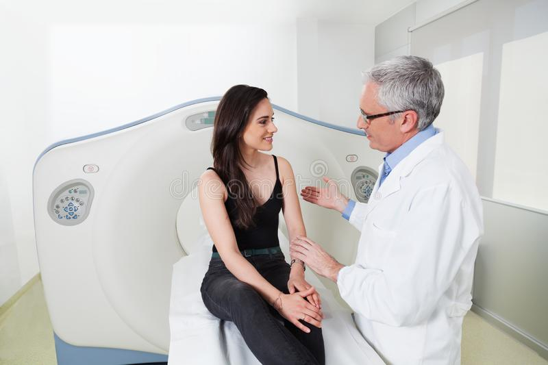 Doctor explains to the young lady in the room of head scan at hospital. A middle aged doctor in white coat explaining the benefits to a women patient the royalty free stock photography