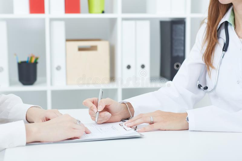 Doctor explaning to her female patient how to fill the medical form at office. Middle section of female doctor explaining to her female patient how to fill the royalty free stock photos