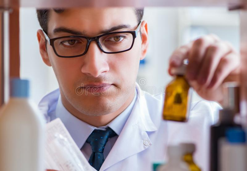 Doctor at farmacy retail shop looking for medicines. The doctor at farmacy retail shop looking for medicines royalty free stock photography