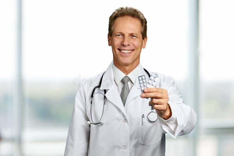 Doctor feliz con dos ampollas de píldoras imagen de archivo