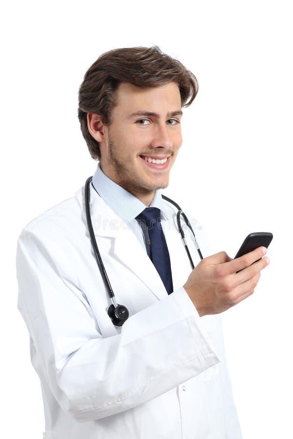 Doctor feliz joven que sostiene un teléfono elegante fotografía de archivo