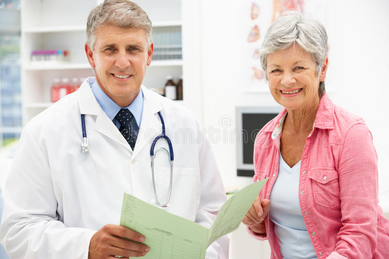 Doctor with female patient. Looking at camera smiling royalty free stock images