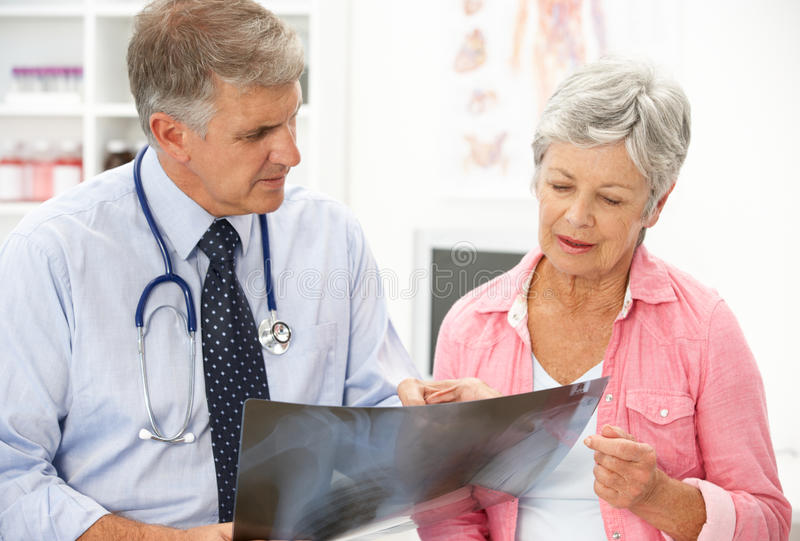 Doctor with female patient. Looking at xray stock photography