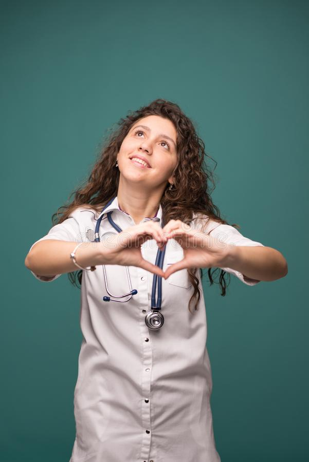 Doctor female shows good sign on green background witn copy space . health concept . vertical photo.  stock photo