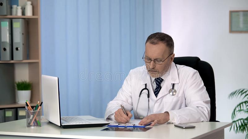 Doctor filling in medical record, considering diagnosis and treatment assignment stock photography