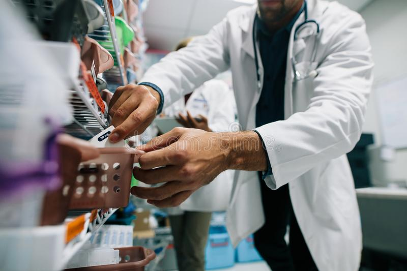 Doctor finding a medicine in hospital pharmacy. Doctor hand finding a medicine in hospital pharmacy. Medical staff looking for medicinal drugs in drugstore royalty free stock photography