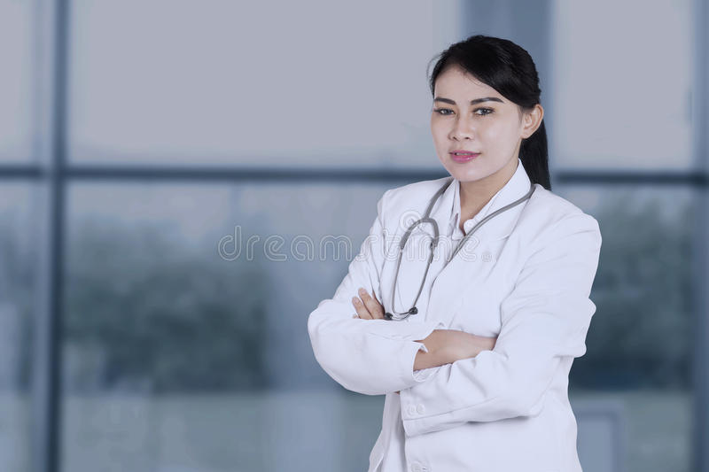 Doctor with folded arms in hospital. Female doctor standing near the window with folded arms and smiling at the camera royalty free stock images