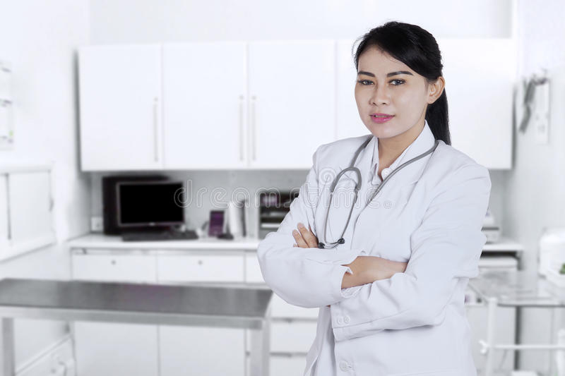 Doctor with folded arms in the laboratory. Portrait of a young Asian doctor standing in the laboratory with folded arms and smiling at the camera stock photography