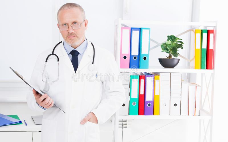 Doctor with folder posing at clinic medical office. Medical insurance royalty free stock images