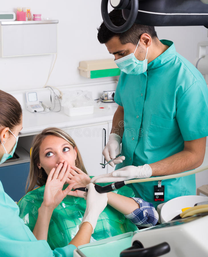 Doctor and frightened patient at clinic. Portrait of dentist and frightened patient at dental clinic stock photo