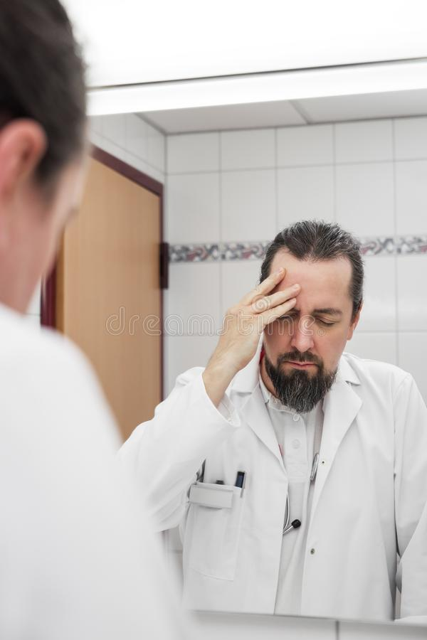 Doctor in front of a mirror have headache. And looks stressed near to an burnout stock photography
