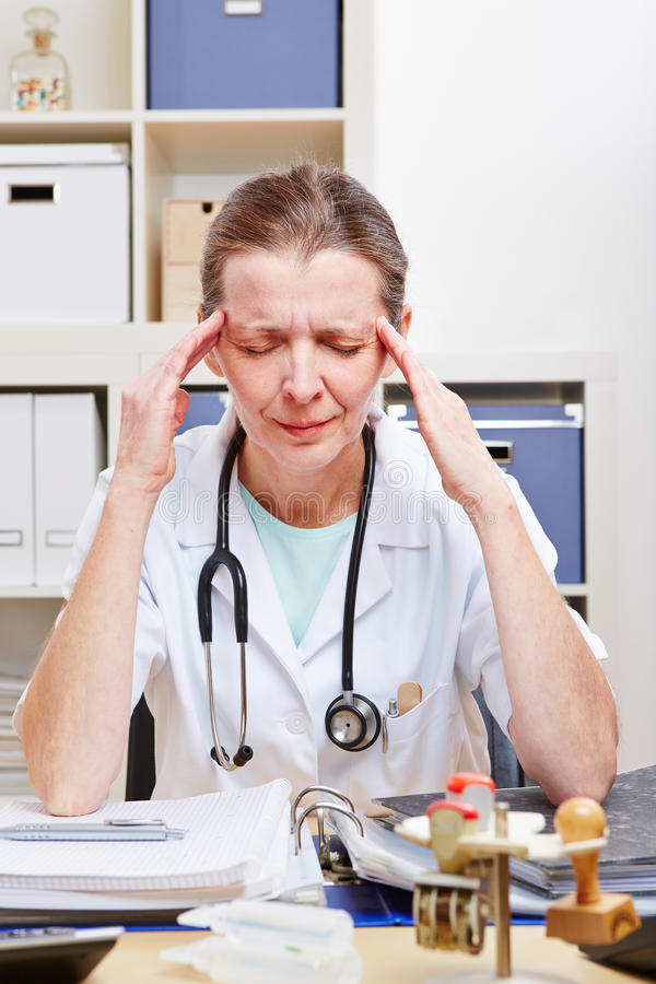 Doctor frustrado con dolor de cabeza fotografía de archivo