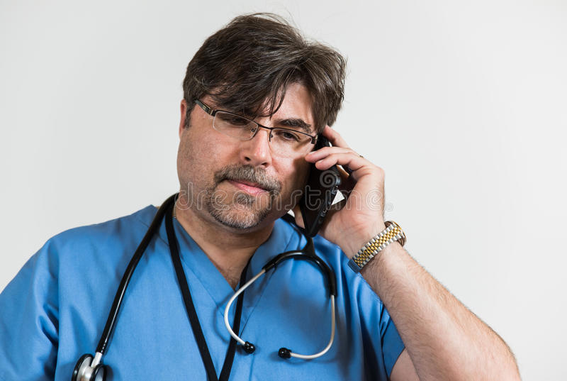 Doctor on Generic Cell Phone. Doctor talking on a generic cell phone looking like he is fielding an important call stock image