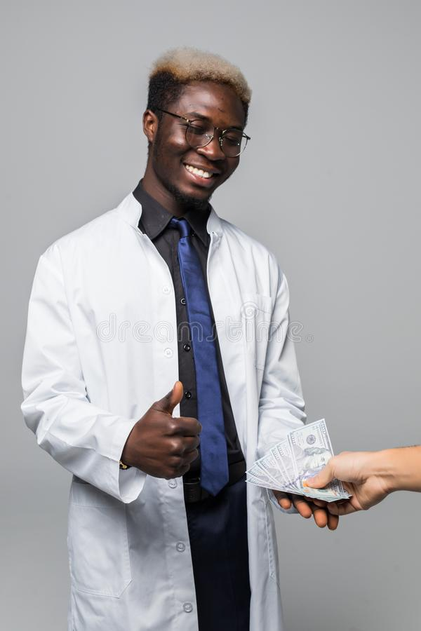 Doctor getting money from man on gray background. Corruption concept stock photos