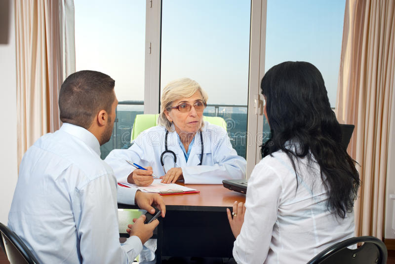 Doctor give medical advices to couple royalty free stock photo