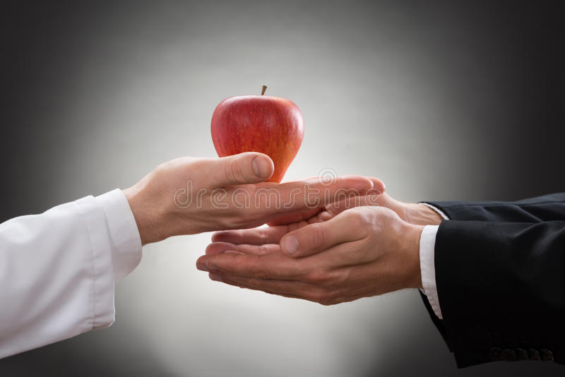 Doctor giving apple to a person. Close-up Of A Doctor's Hand Offering Apple To Another Person stock photography