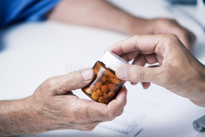 Doctor giving a bottle of pills to a senior man royalty free stock photography