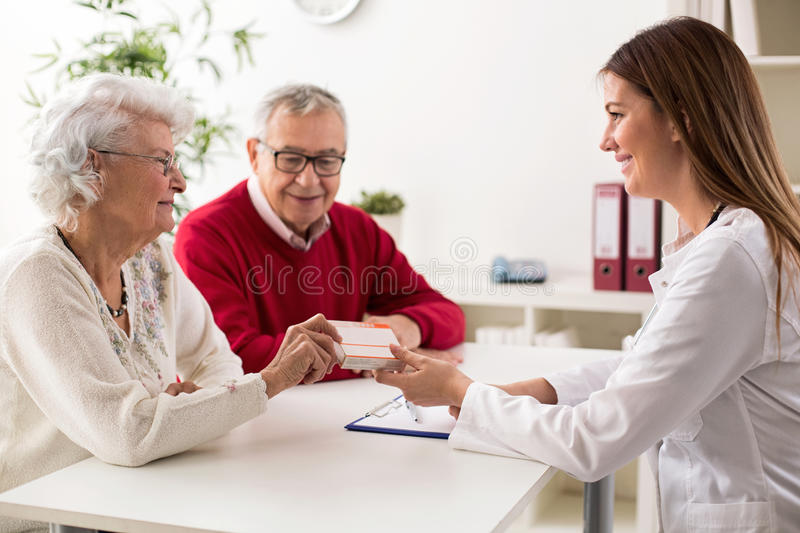 Doctor giving drugs to her senior woman patient royalty free stock photography