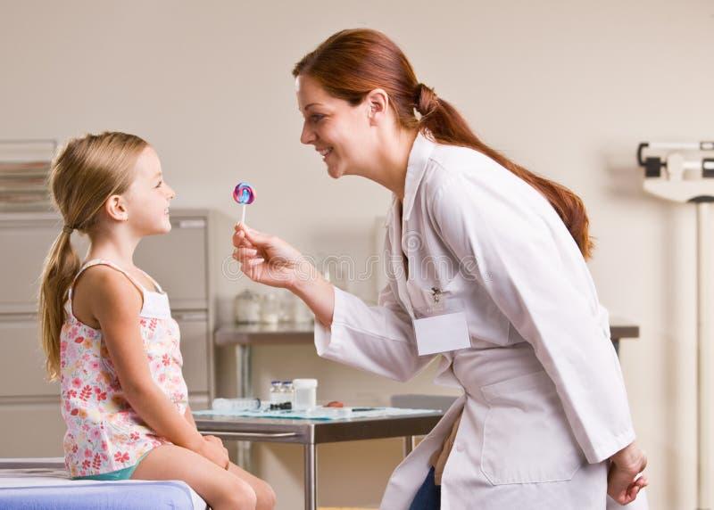 Doctor giving girl lollipop in doctor office stock photos