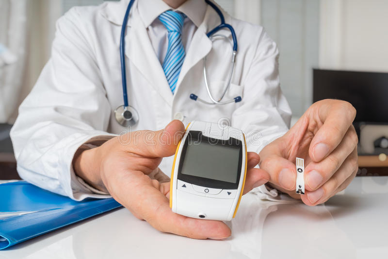 Doctor is giving glucometer to diabetic patient to measure blood sugar. Diabetes concept.  stock photos