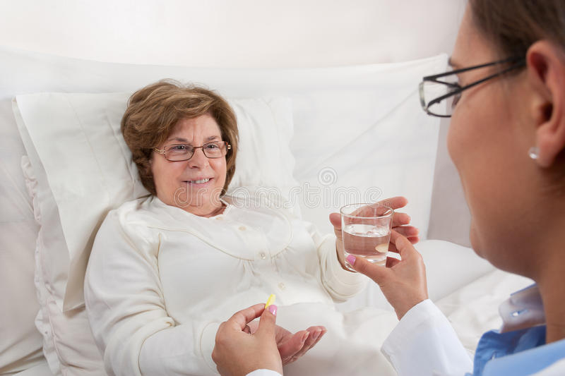 Doctor giving medication to senior patient stock photography