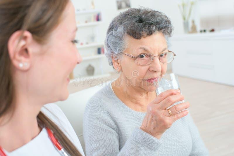Doctor giving medicine pills to elderly woman stock photo