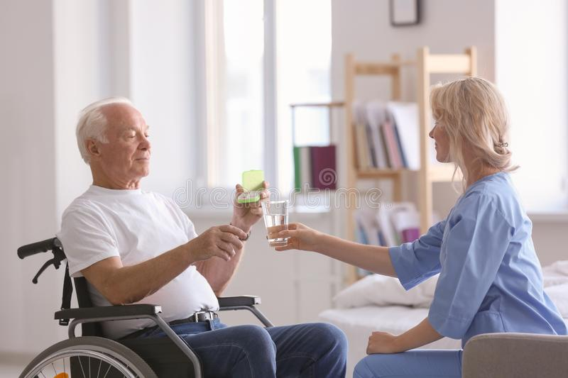 Doctor giving medicine to senior man at home royalty free stock images