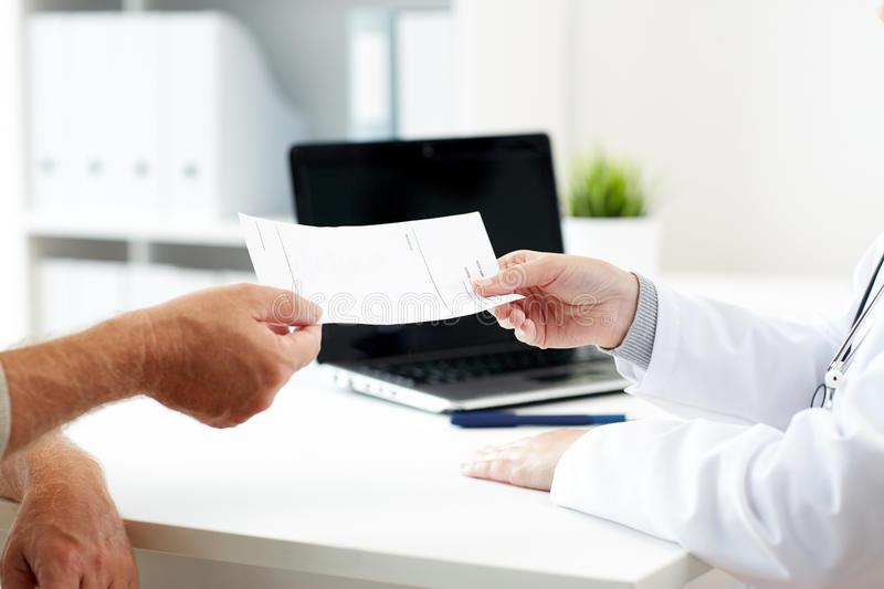 Doctor giving prescription to patient at hospital. Medicine, old age, healthcare and people concept - close up of doctor giving prescription to senior patient at royalty free stock photo