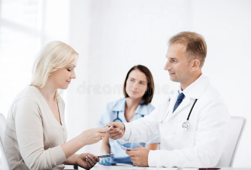 Doctor giving tablets to patient in hospital